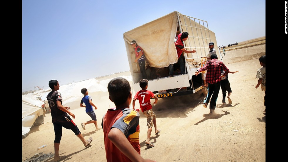 Iraqis run behind a Red Crescent Society truck as it delivers food and other items to a displacement camp in Khazair, Iraq, on Monday, June 30. Many people <a href='http://www.cnn.com/2014/06/13/world/gallery/iraq-under-siege/index.html'>have fled their homes</a> as vast swaths of northern Iraq, including the cities of Mosul and Tal Afar, have fallen to Islamist militants.