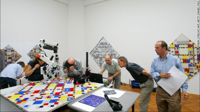 "Specialists examine Piet Mondrian's ""Victory Boogie Woogie"" (1944) in the Gemeentemuseum. The museum contains the world's largest collection of the Dutch artist's work."