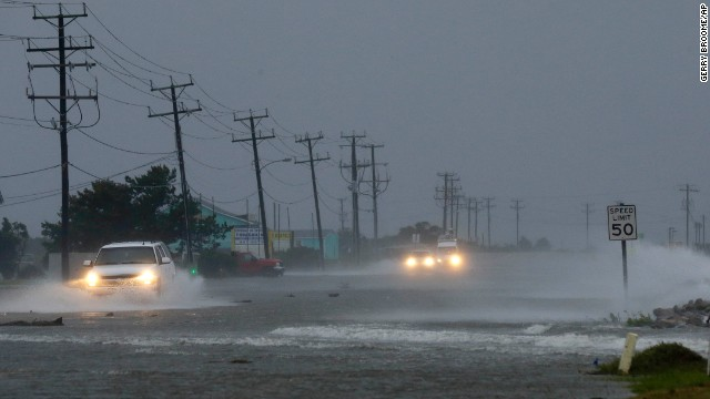 Vehicles drive through a flooded highway in Nags Head, North Carolina on July 4.