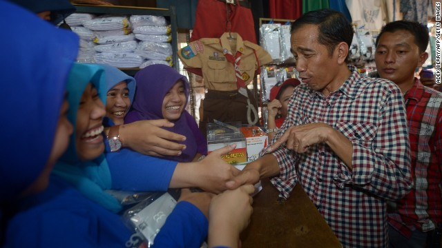 "Presidential candidate Joko ""Jokowi"" Widodo visits a traditional market during his campaign in Jakarta on June 30. Known for his folksy and humble demeanor, Widodo symbolizes a new breed of leadership to his admirers."