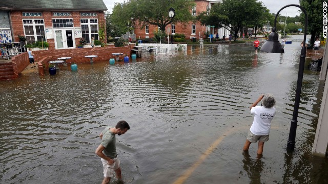 People walk along a flooded street in Manteo, North Carolina, on July 4. Hurricane Arthur made landfall between Cape Lookout and Beaufort, North Carolina, the National Hurricane Center said. It was a Category 2 when it came ashore, but it soon weakened to a Category 1 as it made its way north.