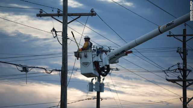 A worker repairs power lines July 4 along Highway 58 in Emerald Isle, North Carolina.