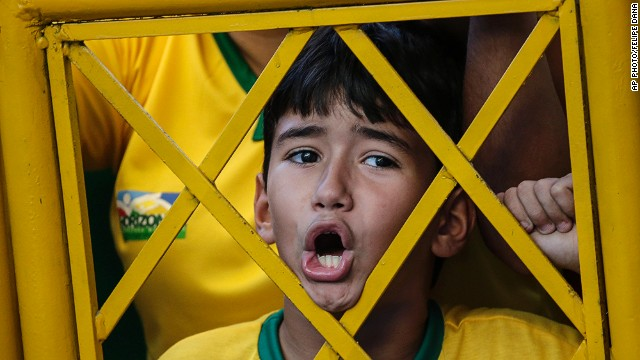 JULY 4 - FORTALEZA, BRAZIL: A young soccer fan shouts from outside the stadium fence during the Brazil national football team's training session on July 3. The host nation will face Colombia today in a<a href='http://cnn.com/2014/07/03/sport/football/world-cup-predictions/index.html'> World Cup quarterfinal match. </a>