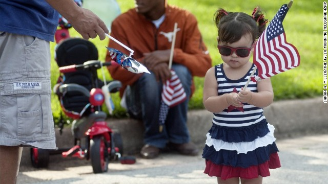 Leah Murphy holds an American flag during the Knollwood Fourth of July parade in Tyler.