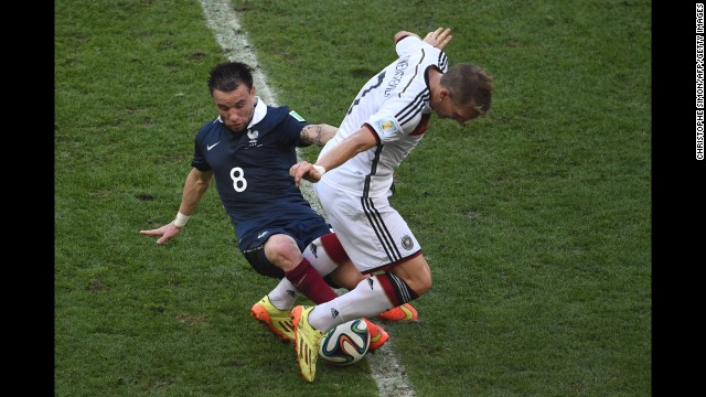 French midfielder Mathieu Valbuena attempts to dispossess Schweinsteiger.