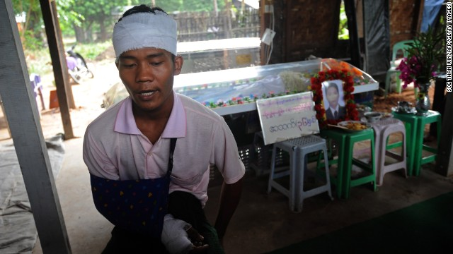 Ko Htwe, who was injured in the riots, sits next to his friend's coffin. Officials say 14 people were injured in the unrest.
