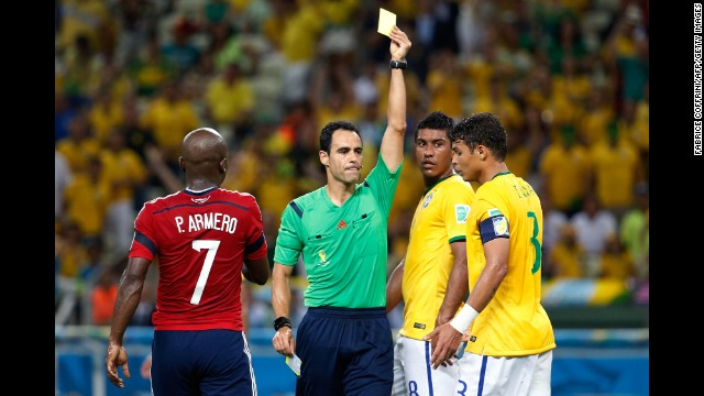 Brazil's Thiago Silva, right, receives a yellow card from referee Carlos Velasco Carballo.