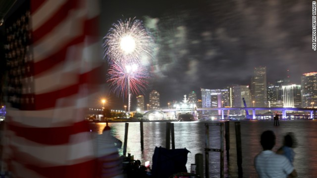 Spectators watch a Fourth of July fireworks display over downtown Miami from Watson Island, Florida.