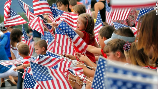 People wave flags as the Independence Day parade rolls down Main Street in Eagar, Arizona.
