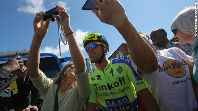 Two-time champion Alberto Contador takes a 'selfie' with some fans before the start of stage two. The 'selfie' fad is making a big impression on this year's Tour, although it has sparked safety fears among the riders.<!-- --> </br>