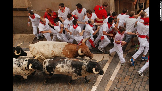 Bulls and revelers run through Pamplona's streets on July 7.