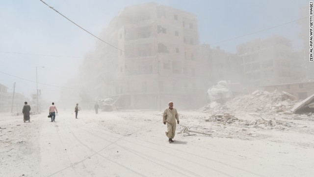 People walk on a dust-filled street after a reported barrel-bomb attack by government forces in Aleppo on Monday, July 7.