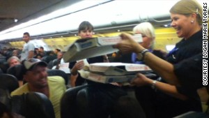 handing out pizza to passengers stranded on a plane
