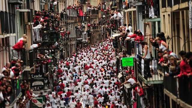 Revelers run on a street in Pamplona on July 9.
