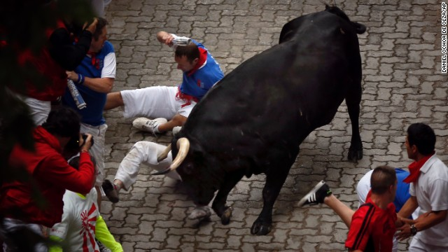 "Bill Hillmann, of Chicago, is gored on his right leg by a bull on July 9. Hillmann has been running in Pamplona for about a decade, and he recently co-authored a book entitled ""Fiesta, How to Survive the Bulls of Pamplona."""