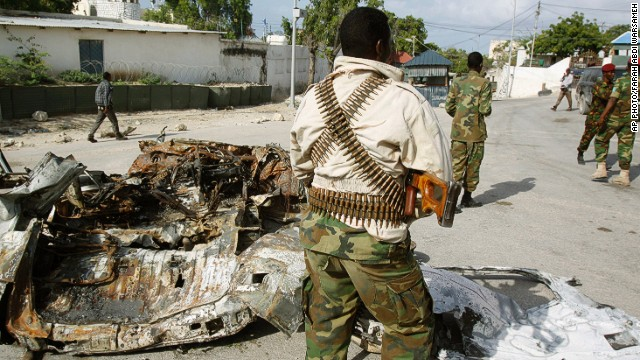 Soldiers stand near the wreckage of a car bomb in Mogadishu, Somalia, on July, 9, 2014.