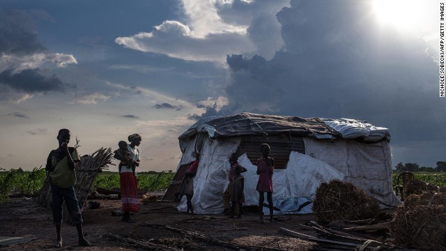 Martha Nyarueni carries one of her children outside her home near the town of Leer, South Sudan, on July 5, 2014.