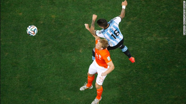 Dirk Kuyt of the Netherlands and Marcos Rojo of Argentina go up for a header.