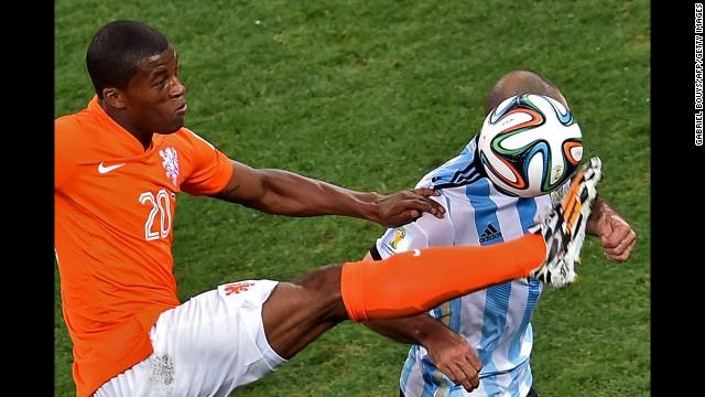 Georginio Wijnaldum of the Netherlands kicks the ball near Mascherano.