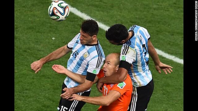 Robben, center, heads the ball next to Argentina defenders Martin Demichelis, left, and Ezequiel Garay.