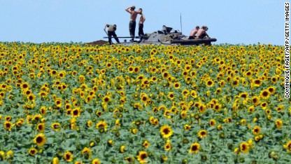 Ukrainian soldiers sit on an armored vehicle as they take up a position in a sunflower field near Donetsk, Ukraine, on Thursday, July 10.