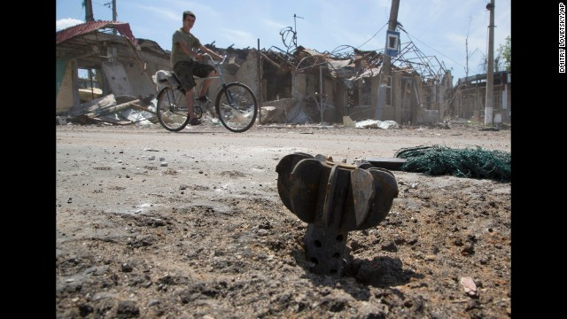 A man rides a bike past the tail of a bombshell outside Slovyansk, Ukraine, on July 10.