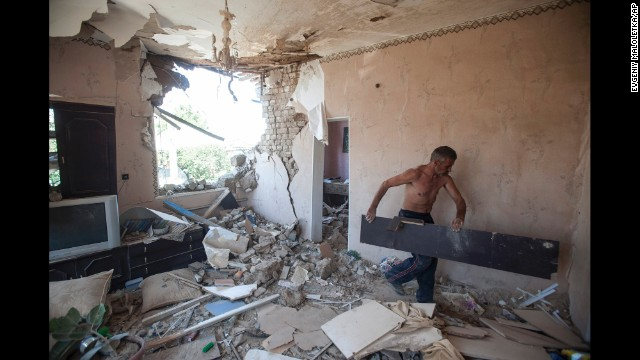 A man cleans up debris in his apartment after a shelling in Slovyansk on July 10.