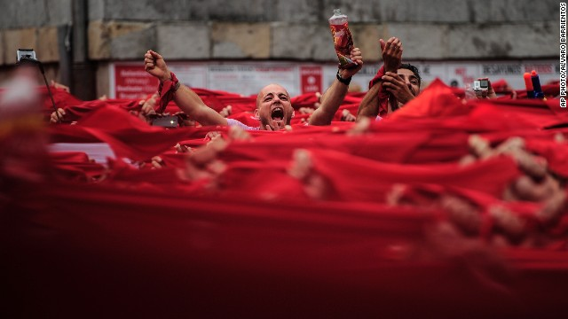 "JULY 10 - PAMPLONA, SPAIN: Revelers hold red kerchiefs during the launch of the ""Chupinazo"" rocket, to mark the official opening of the 2014 San Fermin festival. The running of the bulls was glorified in <a href='http://edition.cnn.com/2014/07/07/opinion/pamplona-bulls-hemingway/'>Ernest Hemingway's 1926 novel ""The Sun Also Rises.""</a>"