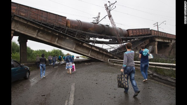 People walk under a destroyed railroad bridge near the village of Novobakhmutivka on Monday, July 7.