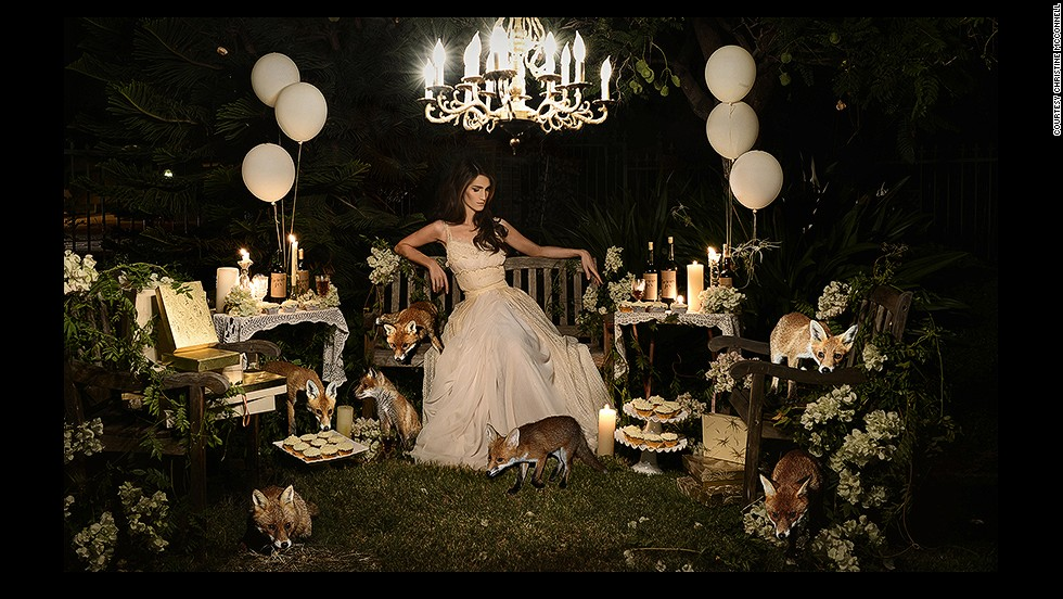 The setting is eerily calm.<!-- --> </br><!-- --> </br>A beautiful girl sits on a bench surrounded by remnants of a party, while wild foxes roam and feast on her baked creations. Her gaze is lowered, and there is a mysterious atmosphere, with dark shadows concealing unknown dangers. <!-- --> </br><!-- --> </br>If you are unsettled by this scene, this is exactly what the photographer <a href='http://instagram.com/christinehmcconnell' target='_blank'>Christine McConnell</a>, pictured above, was trying to achieve. In her images, the Los Angeles-based artist combines the glamor of 1950s pin-ups with Tim Burtone-esque elements of twisted fantasy. <!-- --> </br><!-- --> </br>By <strong><a href='https://twitter.com/M_Veselinovic' target='_blank'>Milena Veselinovic</a></strong>, for CNN