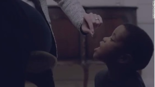 The withdrawn advertisement shows a white woman feeding a young black boy like a pet.