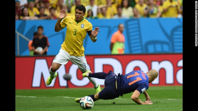 Brazil defender and captain Thiago Silva, left, reacts after fouling Netherlands forward Arjen Robben.