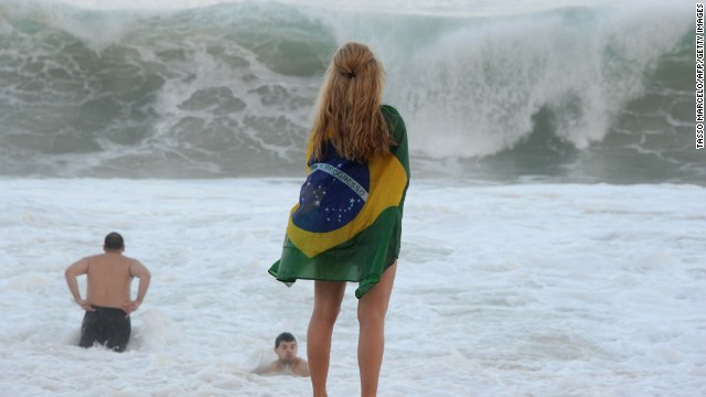 A fan of Brazil stands on the shore of Copacabana beach in Rio de Janeiro.