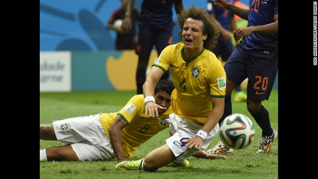 Brazil defender David Luiz, center, falls after a tackle.