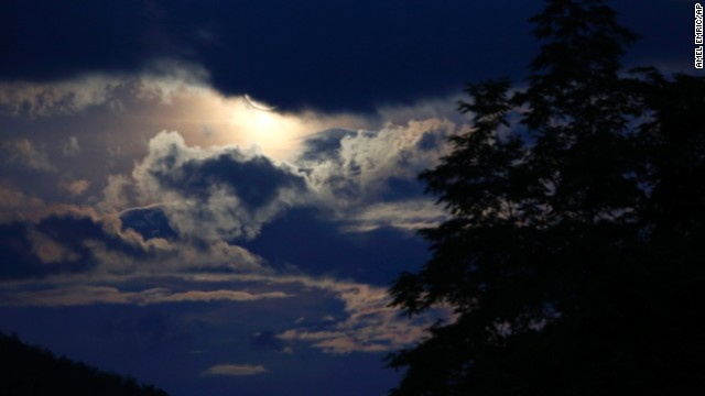The moon casts a glow on clouds over a forest near Sarajevo.