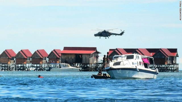 A police helicopter patrols a Sabah resort on July 13 after an attack by gunmen leaves one officer dead and another missing.