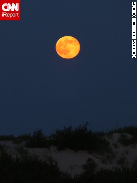 "Over the years, Katherine Murray has taken some nice full moon photos from the <a href='http://ireport.cnn.com/docs/DOC-1152270'>Outer Banks</a> of North Carolina, but capturing an orange moon had eluded her until this weekend. ""I was thrilled to be able to get the actual color as it came over the dunes,"" she said."