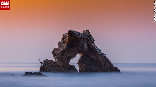 "The Arch Rock is a famous rock formation just off the coast of Corona del Mar State Beach in California. iReporter <a href='http://ireport.cnn.com/docs/DOC-1145896'>Toby Dingle</a> said the feeling of peace and tranquility, ""as well as the fury of the ocean's power, came together in perfect harmony"" for this shot."