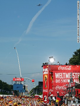 Flying in for a heroes' welcome on Tuesday, the plane carrying Germany's World Cup winners glides over the Brandenburg Gate in Berlin where fans gathered to celebrate their Brazilian success.