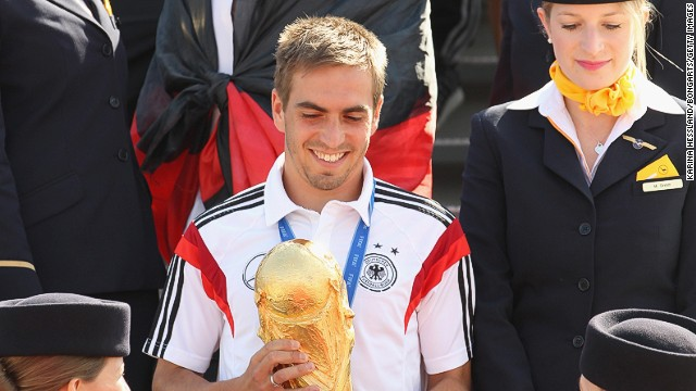 Germany captain Philipp Lahm carries some very special cargo off the plane -- the Jules Rimet Trophy -- as the team land on home soil.