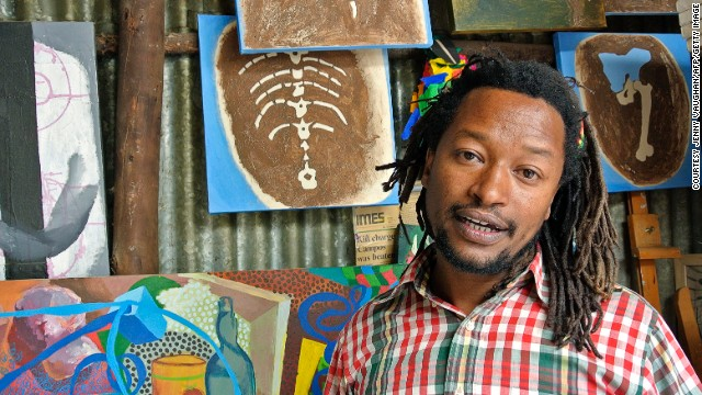Contemporary Ethiopian artist Tamrat Gezahegn poses with some of his paintings at the Netsa Art Village in Addis Ababa, Ethiopia.