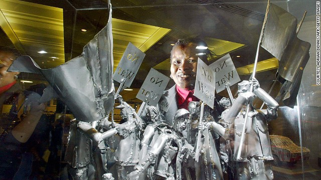 "Nigerian-born artist Sokari Douglas Camp stands with her sculpture ""NO-O-WAR-R, NO-O-WAR-R"" inside London's National Gallery."