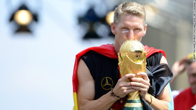 Germany's midfielder Bastian Schweinsteiger kisses the trophy.