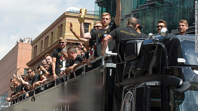 Next stop for the German team is a parade through Berlin. Defender Per Mertesacker shows off the trophy to the adoring crowd.
