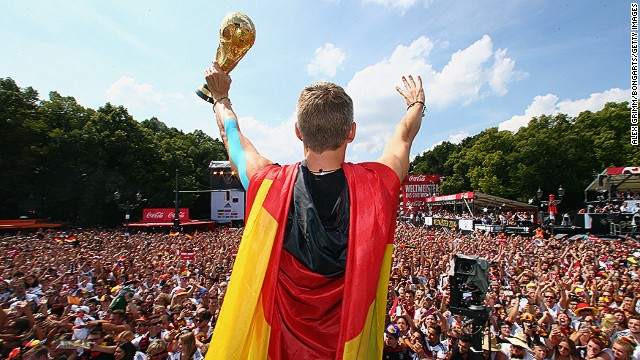 Bastian Schweinsteiger channels Superman with a cape made out of the German flag as he lifts the trophy in front of a packed Berlin crowd.