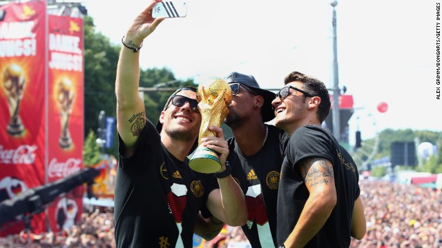 A celebration just isn't the same without a selfie with the World Cup trophy as Lukas Podolski, Jerome Boateng and Mesut Oezil discover.