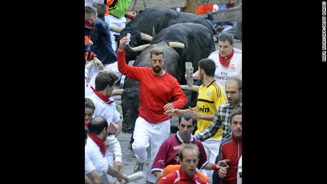 A man takes a selfie Friday, July 11, as he participates in the annual <a href='http://www.cnn.com/2014/07/07/world/gallery/running-of-the-bulls/index.html'>running of the bulls</a> in Pamplona, Spain. The bull run, a 400-year tradition, is part of the San Fermin festival. But according to the city's new rules, carrying any device to record video or take pictures <a href='http://www.cnn.com/2014/07/14/travel/spain-pamplona-selfie/index.html'>is prohibited</a> because it could distract the runner and endanger others.