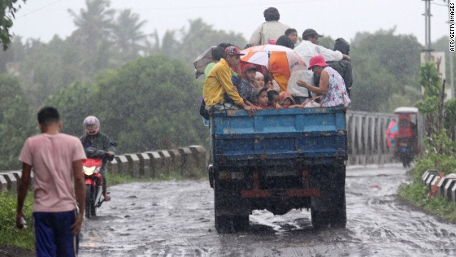 Residents ride on a truck as they are evacuated from the approaching Typhoon Rammasun in Legazpi City, southeast of Manila, on July 15.