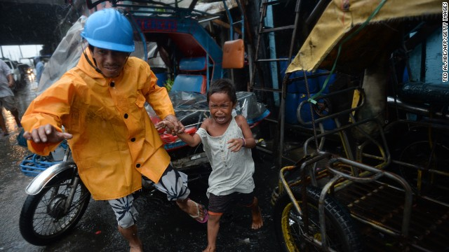 A village official leads a child as he is evacuated from their house at an informal settlers' area as Typhoon Rammasun lashes rain on Manila on July 16, 2014.
