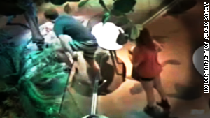 In surveillance images, a male in striped shorts is seen climbing over a low glass barrier.